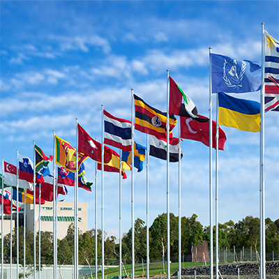 International flags flying against a blue sky.