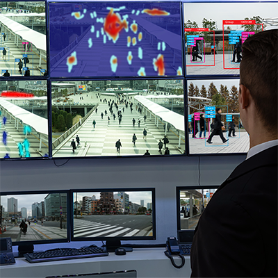 Person reviewing multiple security camera monitors, one in infrared.